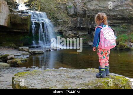 Ein 3 Jahre altes Mädchen Uhren Wasser cascading bei West Burton fällt in den Yorkshire Dales National Park - Stockfoto