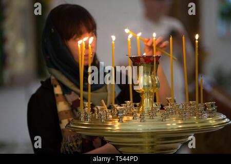 Kerzen in der Kirche. Zu Gott beten. Eine Frau mit Kopftuch in die Kirche ligh - Stockfoto