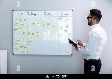 Seitenansicht des Geschäftsmannes Schreiben auf Haftnotizen zu White Board In Office angeschlossen - Stockfoto