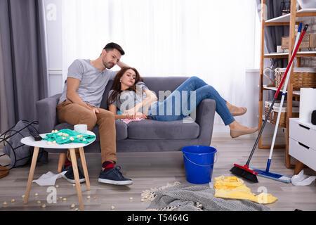 Lächelndes Paar entspannt auf einem Sofa im Wohnzimmer zu Hause unordentlich - Stockfoto