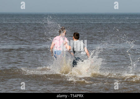 Southport, Merseyside, UK. 21. April 2019. Abkühlung. Einen tollen Tag am Meer wie Alfie & Ellie Evans Abkühlen, die in der ankommenden Gezeiten- Wasser spritzen, die entlang der Küste von Southport Strand in Merseyside. Credit: cernan Elias/Alamy leben Nachrichten - Stockfoto