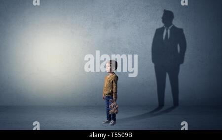 Kind vor, dass er Geschäftsmann und illustriert seine Zukunft in einem großen Schatten. - Stockfoto
