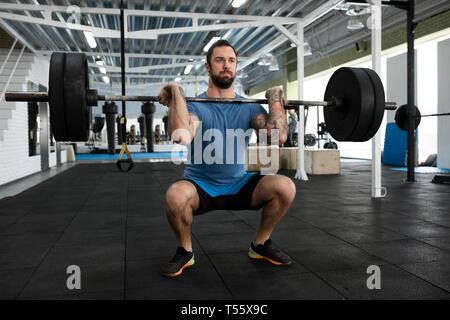 Mitte der erwachsene Mann Gewichtheben in der Turnhalle