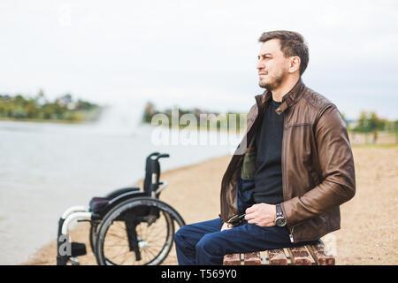 Ein junger Mann sitzt auf einer Bank am See, neben seinem Rollstuhl. - Stockfoto