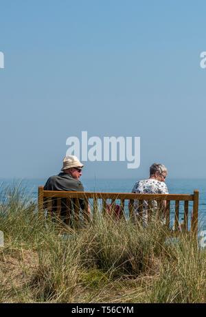 Ein älteres Paar auf einer Bank sitzen am Meer an einem warmen sonnigen Tag im Sommer im Urlaub auf der Insel Wight. - Stockfoto