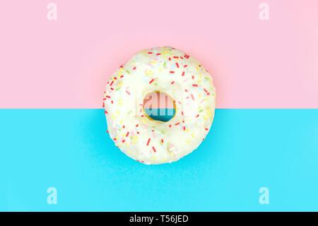 Weiße, runde Donut auf Rosa und blauem Hintergrund. Flach, Ansicht von oben. - Stockfoto