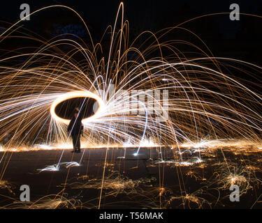 Man spinnen Wunderkerzen Feuerwerk bei Nacht aus Stahl Wolle - Stockfoto
