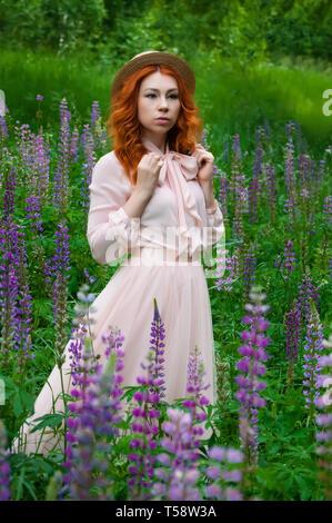 Eine schöne rothaarige Frau steht und stellt in einem Feld von lila Lupinen und geniesst die Aussicht im Frühjahr - Stockfoto