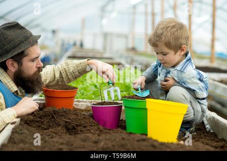 Verguss Blumen. Vater und Sohn Blumenerde Blumenerde Blumen Blumen. mit Kind und dessen Vater. Vater und kleiner Junge Blumenerde Blumen im Gewächshaus - Stockfoto