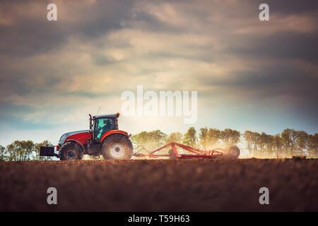 Landwirt in Vorbereitung der Flächen mit Saatbeet Grubber Traktor - Stockfoto