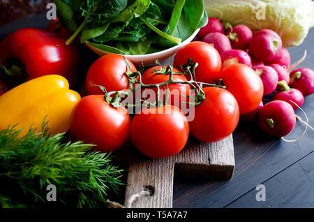 Tomaten, Gurken, rote gelbe und orange Paprika, Radieschen, Zwiebeln, Kräutern auf alten rostigen dunklen Hintergrund mit natürlichem Licht. Sortiment an frischen veget - Stockfoto