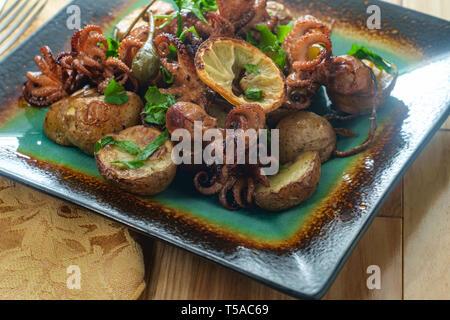 Portugiesische Polvo A Lagareiro Gegrillter Tintenfisch mit gebackenen Fischkartoffeln und Kapern Beeren - Stockfoto