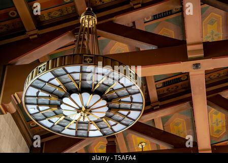 Nahaufnahme von Messing Art Deco Leuchte in der Los Angeles Union Station, Bahnhof, mit Details der Mission Revival bemalten Decke und Holzbalken. - Stockfoto