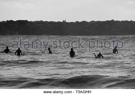 Sechs Surfer auf ihre Pension Warten auf die nächste Welle gesetzt, während am frühen Morgen Surfen; als Paar Spaziergang entlang einer Wand im Hintergrund. - Stockfoto