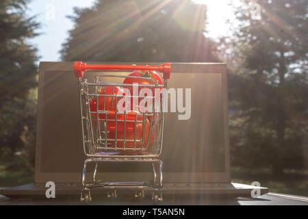 Konzept der Online Einkaufen. Ein Miniatur Warenkorb mit Tomaten steht ein Notebook. - Stockfoto