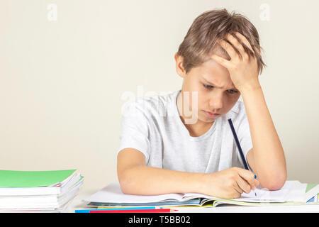 Traurige junge Hausaufgaben machen. Bildung, Schule, Lernschwierigkeiten Konzept - Stockfoto