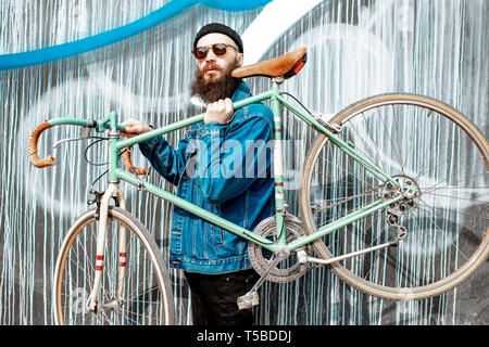 Porträt eines eleganten bärtigen Mann in Jacke und Hut mit retro Fahrrad auf die bunte Wand Hintergrund gekleidet - Stockfoto
