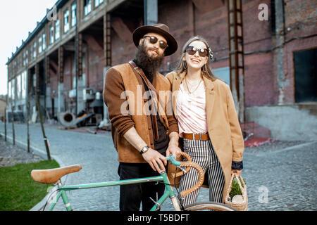 Porträt einer stilvollen Mann und Frau gemeinsam mit retro Fahrrad draußen auf der industriellen städtischen Hintergrund - Stockfoto