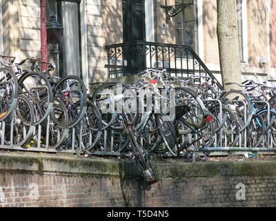 Reihe von Fahrrädern in Regalen an der Seite des Kanals geparkt mit einem prekär hängen über den Rand; Amsterdam, April 2019 - Stockfoto