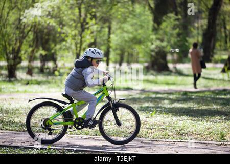 Kleiner Junge lernt ein Fahrrad im Park zu fahren. Süße Junge in Sonnenbrille reitet ein Fahrrad. Glücklich lächelnde Kind in Helm Reiten Radfahren. - Stockfoto