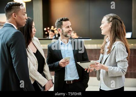 Geschäftsleuten stehen und diskutieren in der Hotellobby - Stockfoto