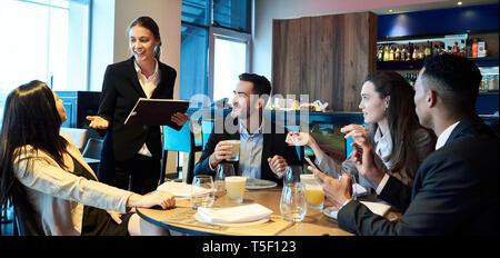 Kellnerin die Bestellungen von Geschäftsleuten in bar - Stockfoto