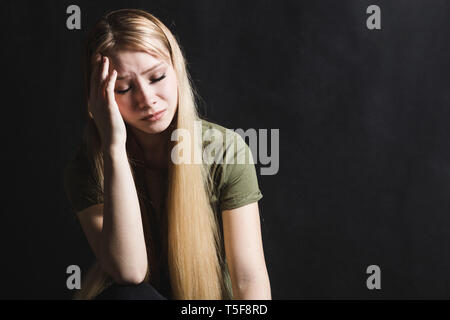 Traurige junge Frau, die in einem schwarzen Hintergrund zu Schrei - Stockfoto