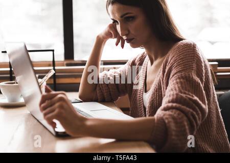 Attraktive junge Frau sitzt an einem Tisch in einem Café bei einer Tasse Kaffee und genießt einen Laptop - Stockfoto