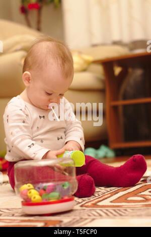 Ein kleines Kind sitzt auf dem Boden im Zimmer und spielen mit Ohr klemmt - Stockfoto