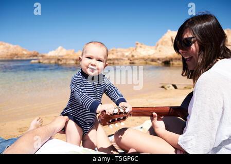 Spanien, Menorca, Portrait von lächelnden kleinen Jungen mit den Eltern am Strand - Stockfoto