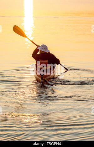 Aktive, unabhängige ältere Mann Kajakfahren im Meer bei Sonnenaufgang oder Sonnenuntergang. Outdoor Adventure Sport genießen, gesunden Ruhestand Lebensstile in der wunderschönen Natur. - Stockfoto