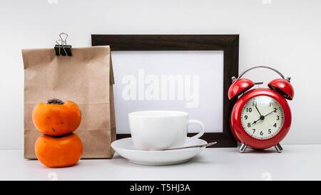 Nach oben Dark Photo Frame, rot Wecker, Papiertüten mit der Aufschrift Frühstück, zwei persimonen und weiße Tasse mit Untertasse von Kaffee auf eine leichte bac Mock - Stockfoto
