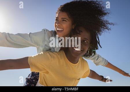 Junger Mann, Frau, Huckepack am Strand - Stockfoto