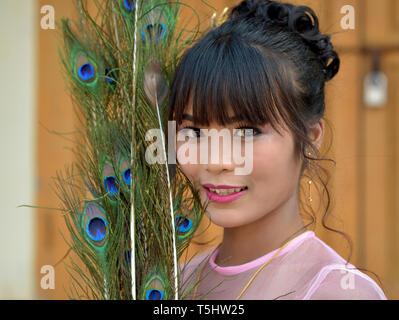 Schönen jungen burmesischen Frau mit Pfauenfedern posiert für die Kamera. - Stockfoto