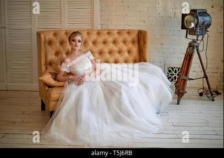 Eine schöne zierliche Blondine sitzt auf der Couch. Die Braut in einem Spitzen Kleid.'s Braut morgen - Stockfoto