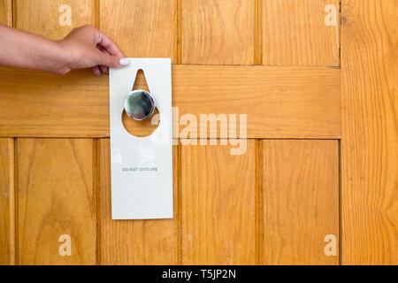 Weibliche Hand hängt ein Schild an der Tür nicht im Hotel stören. - Stockfoto