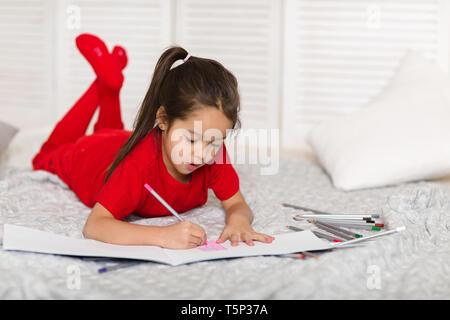 Süßes kleines Kind Mädchen in roten Schlafanzug zieht mit Bleistift zu Hause - Stockfoto