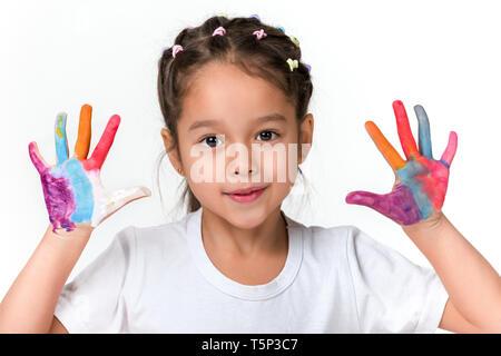 Süßes kleines Kind Mädchen mit Händen in bunte Farbe auf weißem Hintergrund gemalt. - Stockfoto