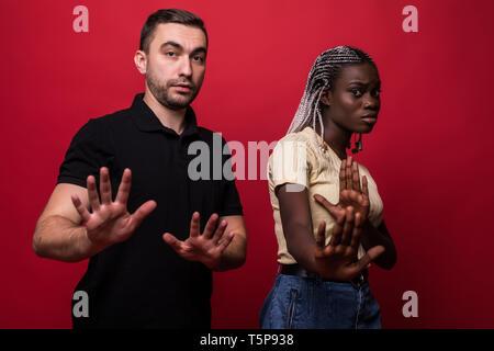 Portrait von schockiert interracial Paare: Afrikanische Frau und kaukasischen Mann zusammen gegen die Rote Wand, die im Gesicht, an der Kamera mit der Suche - Stockfoto