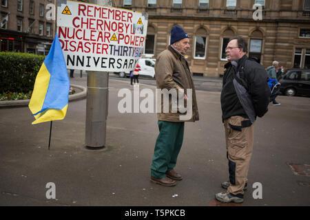 Glasgow, Schottland, 26. April 2019. 78-Jahre alt Jim Gillies (Links) steht auf dem George Square mit seinem Plakat 1986 in Erinnerung an die Reaktorkatastrophe von Tschernobyl in der Ukraine. Heute ist der 33. Jahrestag der Katastrophe und Jim Gillies hat das Disaster Tag markiert, indem er mit seinem Plakat auf dem Platz je Jahr, da, sowie mehr als 20.000 £ GBP Spenden an einem Krankenhaus in der Ukraine, ein Land, das er jetzt ca. 20 Mal besucht hat. Quelle: Jeremy Sutton-hibbert/Alamy leben Nachrichten - Stockfoto
