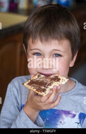 Eine Nahaufnahme portrait einer niedlichen blauäugige Kind essen eine matzoh Cracker mit Schokolade verteilt.