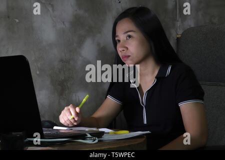 Asiatische Frau von zu Hause spät in der Nacht arbeiten bei schlechter Beleuchtung. (Dark Light haben einige Körner und Lärm) - Stockfoto