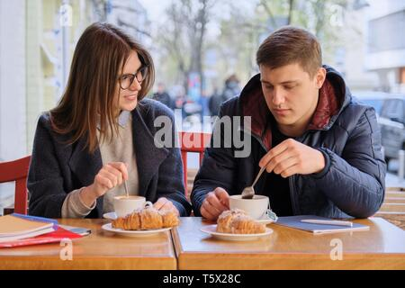 Junge männliche und weibliche Freunde Studenten im Café draußen sitzen, reden, trinken Kaffee, Tee, essen Croissants. Auf tisch Lehrbücher, Notebooks, Stadt - Stockfoto