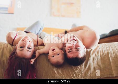 Glückliche Eltern mit entzückenden kleinen Baby Mädchen sitzen auf der Couch zu Hause und genießt die Elternschaft, junge, glückliche Familie, neues Leben Konzept. - Stockfoto