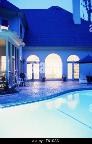 Upscale Suburban House in der Nacht mit beleuchtetem Pool- und Terrassenbereich, USA - Stockfoto