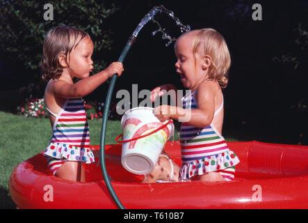 Triplet Mädchen spielen in einem Planschbecken, USA - Stockfoto