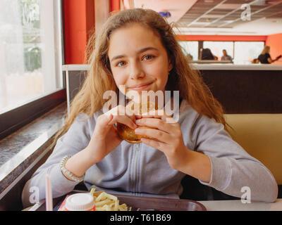 Hübsche, junge Teen Girl mit Appetit essen Hamburger in einem Cafe