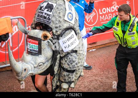 London, Großbritannien. 28. Apil 2019. Rhino Harry, ave für die Ausführung der Rhino', an der Ziellinie geholfen wird. Über 40.000 Starter sind wieder einmal konkurrieren in der Virgin London Marathon, einschließlich derer, die auf der Rasse für Nächstenliebe, in Clubs, in Erinnerung an die Lieben und als persönliche Lebenszeit Ziele. Credit: Imageplotter/Alamy leben Nachrichten - Stockfoto