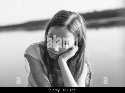 Schwarz-weiß-Porträt von Traurig schönen jugendlich Mädchen mit ernsten Gesicht am Meer bei Sonnenuntergang - Stockfoto