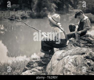 1930er Jahre zwei Jungs sitzen auf den Felsen Angeln im Teich mit Pfosten aus Zweigen und STRING-a5121 HAR 001 HARS FREIZEIT- UND RÜCKANSICHT GESCHWISTER GEMACHT STROHHUT HUCK FINN STICKS ZWEIGE ANGELN BIB OVERALLS TOM SAWYER RÜCKANSICHT HUCKLEBERRY FINN JUGENDLICHE PRE-TEEN PRE-TEEN BOY ENTSPANNUNG ZWEISAMKEIT SCHWARZ UND WEISS KAUKASISCHEN ETHNIE HAR 001 ALTMODISCH - Stockfoto